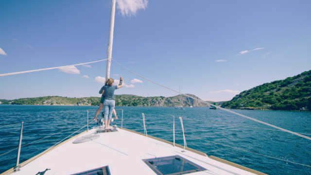 ws mother and daughter waves their hands in the sea breeze - ponte di una nave video stock e b–roll