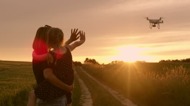 ws mother and daughter waving to a drone flying at sunset - rural scene stock videos & royalty-free footage