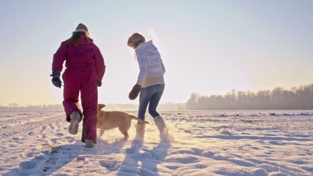 WS Mother And Daughter With A Puppy In Snow