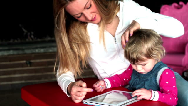 stockvideo's en b-roll-footage met mother and daughter with digital tablet - pjphoto69