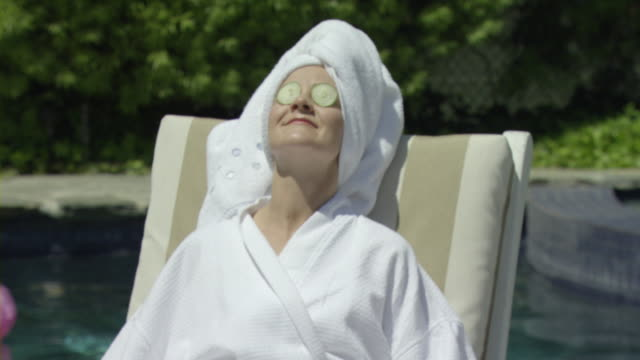 td pan ms mother and daughter (8-9) with face masks sitting on deckchairs by pool, encino, california - cucumber stock videos and b-roll footage