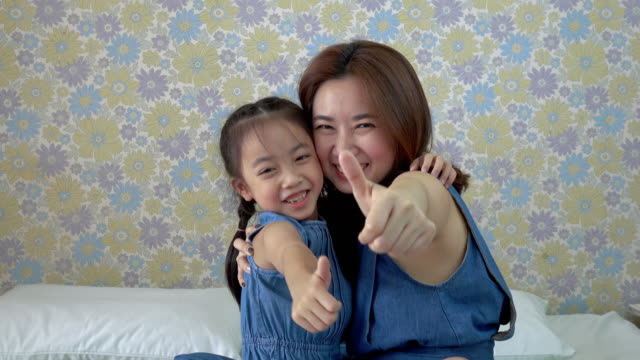 Mother and daughter with thumbs up