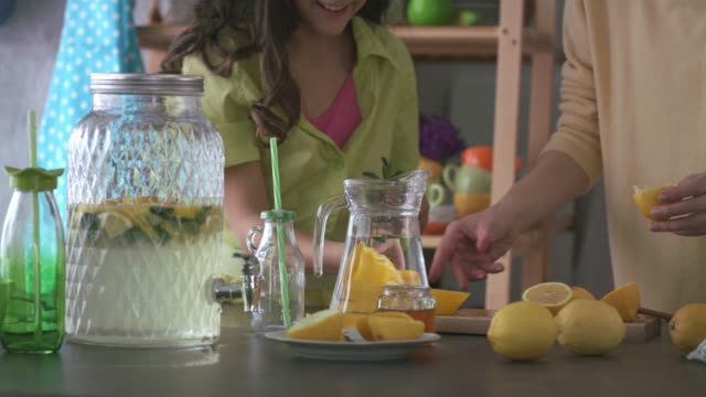 mother and daughter working as a team while making a lemonade - traditional lemonade stock videos & royalty-free footage