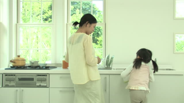 Mother and daughter working in kitchen