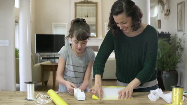Mother and daughter wrapping a box