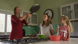 Mother and daughters cooking crepes together