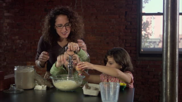 MS Mother and daughters (6-9) cooking in kitchen / Jersey City, New Jersey, USA