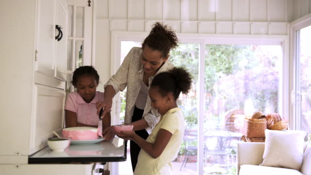 mother and daughters decorating cake with icing - decorating a cake stock videos and b-roll footage