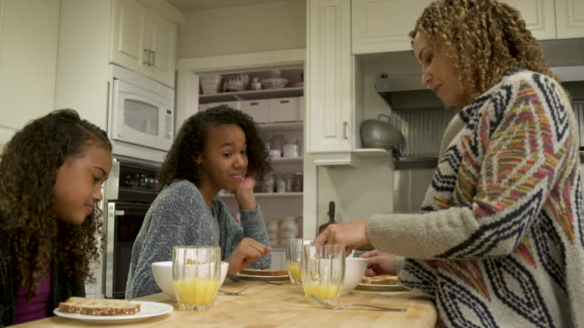 vídeos de stock, filmes e b-roll de mother and daughters having breakfast together. - interior