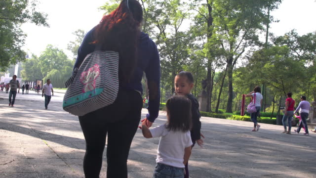stockvideo's en b-roll-footage met mother and daughters holding hands at a park in mexico - alleenstaande moeder