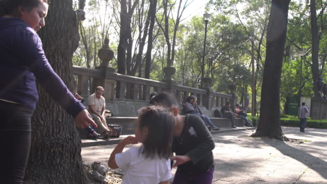 mother and daughters holding hands at a park in mexico - mit handkamera stock-videos und b-roll-filmmaterial