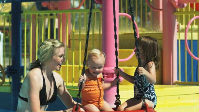 mother and daughters in a pool - tyre swing stock videos & royalty-free footage