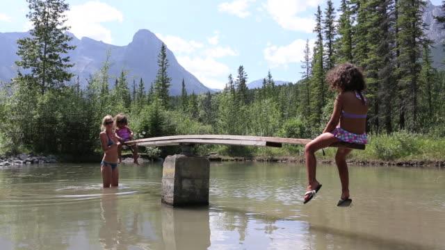 母と娘は浅い池で一緒に遊ぶ - 10歳から11歳点の映像素材/bロール