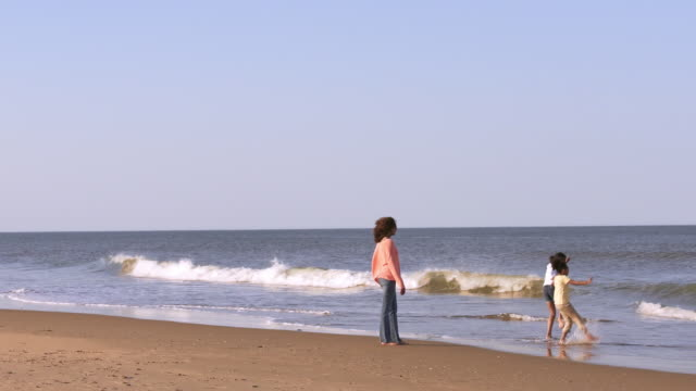 Mother and daughters playing on beach in ocean waves