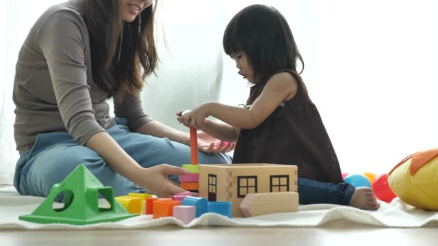 mother and daughters playing toy in living room - ethnicity stock videos & royalty-free footage