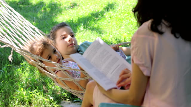 mother and daughters reading books on a hammock, a girl lying in a hammock, 2 girls lying in a hammock, reading a book at the backyard, girl sleeping with her mother reading a book in hammock - hammock stock videos & royalty-free footage