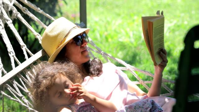vídeos de stock, filmes e b-roll de mãe e filhas lendo livros em uma rede, uma menina deitada em uma rede, duas meninas deitadas em uma rede, lendo um livro no quintal, menina dormindo com sua mãe lendo um livro na rede - rede de dormir