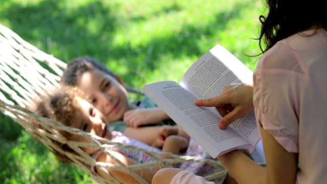 mother and daughters reading books on a hammock, a girl lying in a hammock, 2 girls lying in a hammock, reading a book at the backyard, girl sleeping with her mother reading a book in hammock - resting stock videos & royalty-free footage