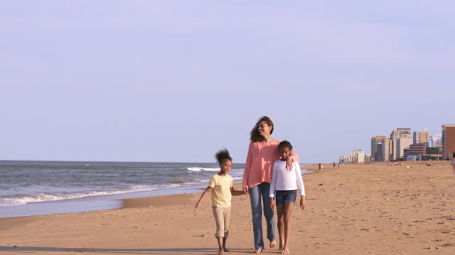 mother and daughters strolling on resort beach - virginia beach stock videos & royalty-free footage
