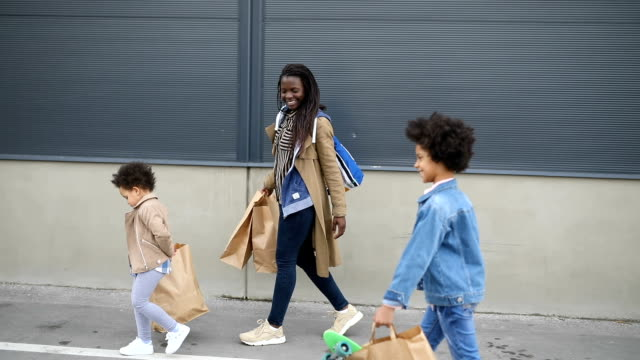 mother and daughters walking towards car carrying shopping bags on a parking loft - family with two children stock videos & royalty-free footage