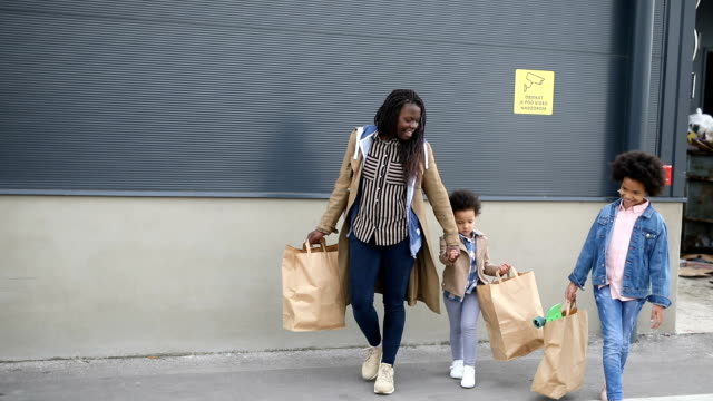 mother and daughters walking towards car carrying shopping bags on a parking loft - single parent family stock videos & royalty-free footage
