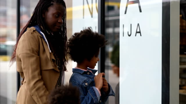 mother and daughters window shopping at retail park - single mother stock videos & royalty-free footage