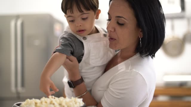 mother and down syndrome son eating popcorn at home - snack stock videos & royalty-free footage