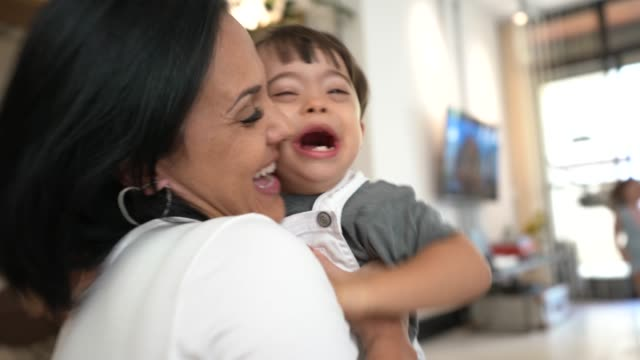 mother and down syndrome son embracing at home - sindrome di down video stock e b–roll