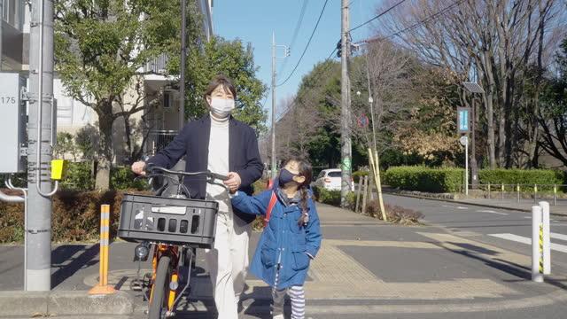 朝、通りを歩く母と小学生。学校に行く娘を働きに行く母親 - 新学期点の映像素材/bロール