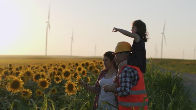 eine mutter und ein vater ingenieur, hält seine tochter in den armen und bleiben zwischen den windkraftanlagen in einem sonnenblumenfeld - fuel and power generation stock-videos und b-roll-filmmaterial