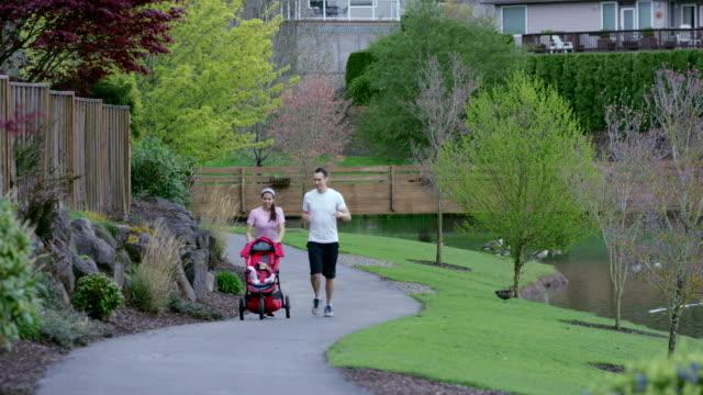 Madre e padre di esercizio fisico con il suo nuovo bambino nel Passeggino