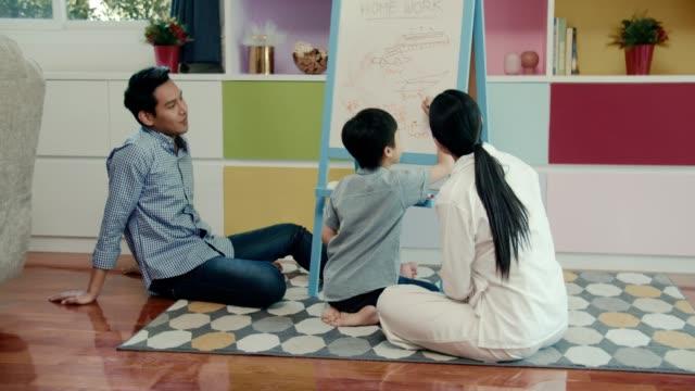 vidéos et rushes de mère et père à la maison l'éducation de son fils - son