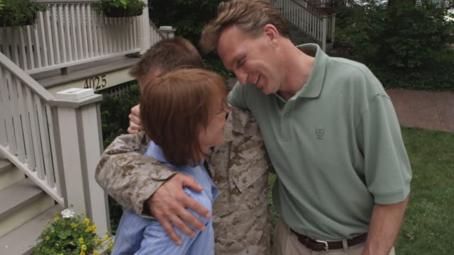 stockvideo's en b-roll-footage met sm ms portrait mother and father hugging returning soldier son in front of house/ chicago, il - 45 49 jaar