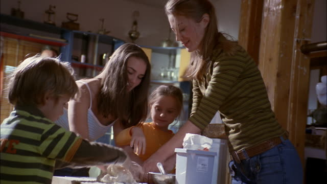 A mother and father instruct their children on how to knead dough.