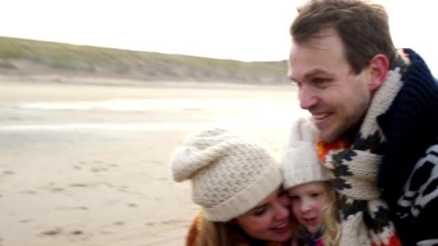 vidéos et rushes de ms ma mère et père embrasser fille sur la plage - fille de