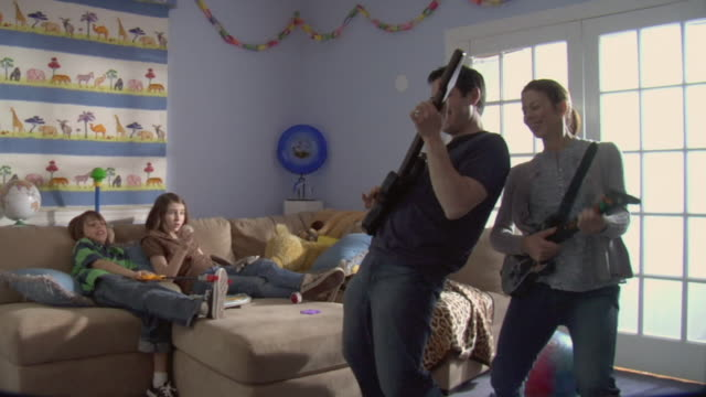 vídeos y material grabado en eventos de stock de ms mother and father playing guitar hero as son and daughter sit on sofa and laugh at them/ white plains, new york - daughter