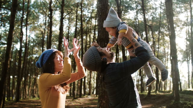 Mother and father playing with child in forest in morning.