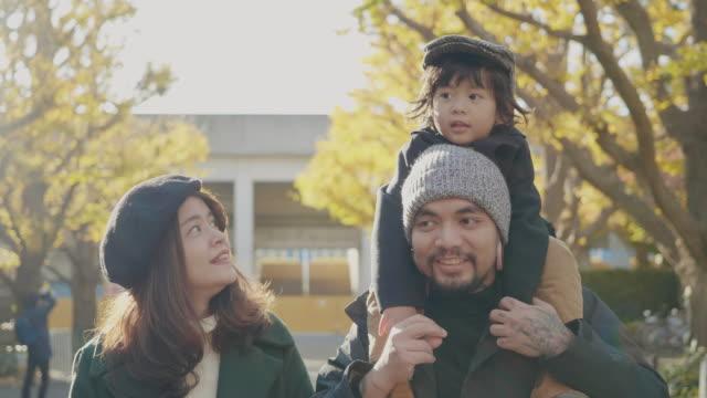 mamma och pappa leker med barn i tokyo city på morgonen. - tvåföräldersfamilj bildbanksvideor och videomaterial från bakom kulisserna
