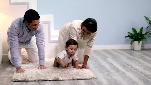 mother and father playing with their baby boy, delhi, india - flooring stock videos & royalty-free footage