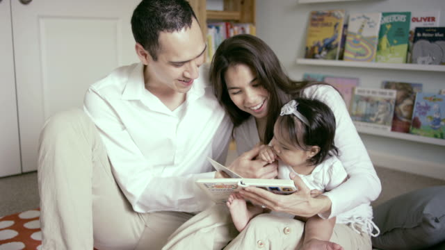 Mother and Father reading with their baby in bedroom