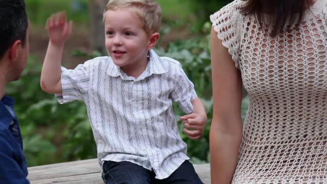 vídeos de stock, filmes e b-roll de ms r/f pan mother and father sitting with son at outdoor picnic table son hugging father - desaparecer gradualmente