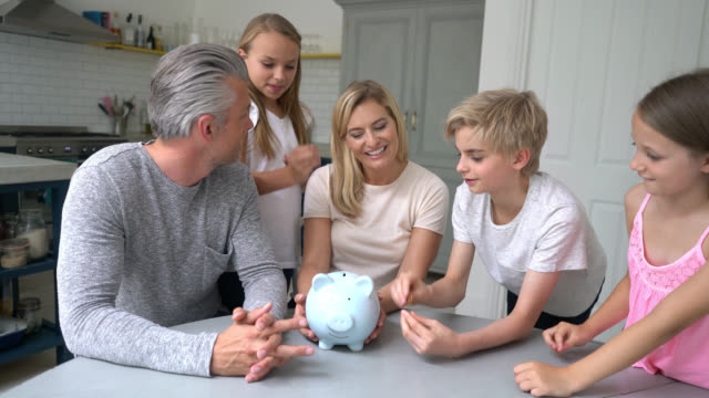 Mother and father teaching their children to save money