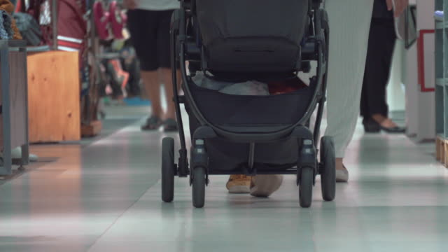 mother and father walks with the stroller and baby in shopping mall - pushchair stock videos and b-roll footage