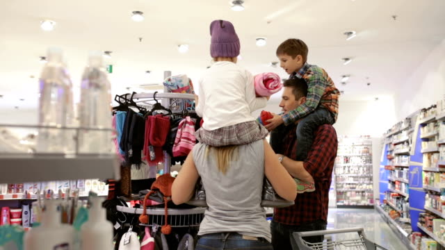 mother and father with kids choosing warm clothing in supermarket, panning shot - sitting stock videos & royalty-free footage