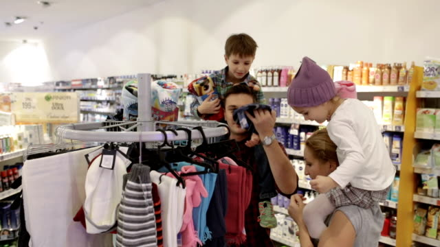 Mother and father with kids choosing warm clothing in supermarket, panning shot