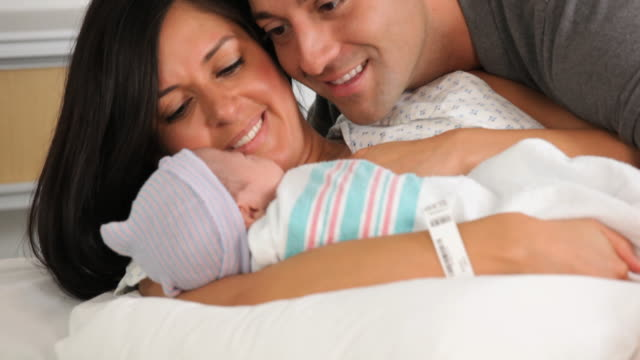 CU TU Mother and Father with Newborn Laying in Hospital Bed / Richmond, Virginia, USA