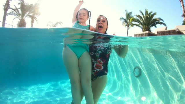 mother and girl with down syndrome, in swimming pool - intellectual disability stock videos & royalty-free footage