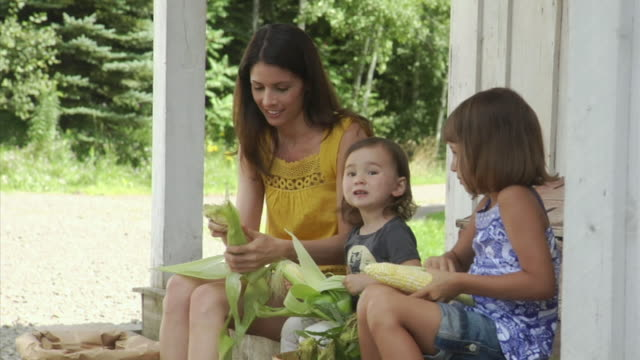 ms mother and girls (4-5 years, 18-23 months) shucking corn on porch, bovina center, new york, usa - 25 29 years stock videos & royalty-free footage