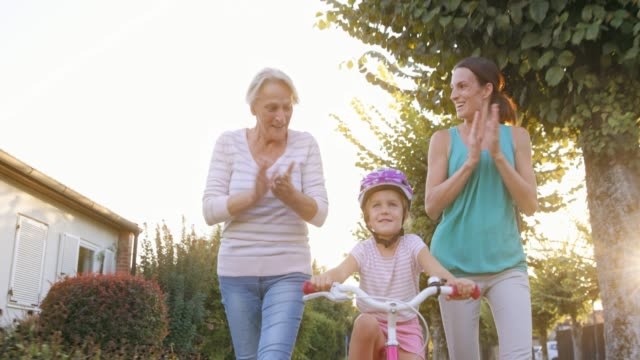 slo mo mother and grandmother teaching the little girl ride the bike and cheering for her - vest stock videos & royalty-free footage