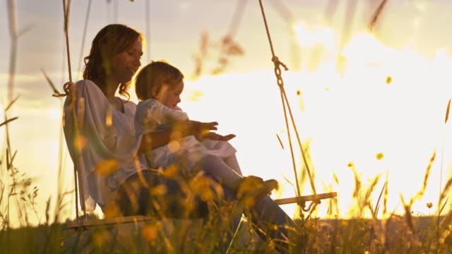 vídeos de stock, filmes e b-roll de slo mo mãe e seu bebê menina balançar ao pôr-do-sol - bebês meninas